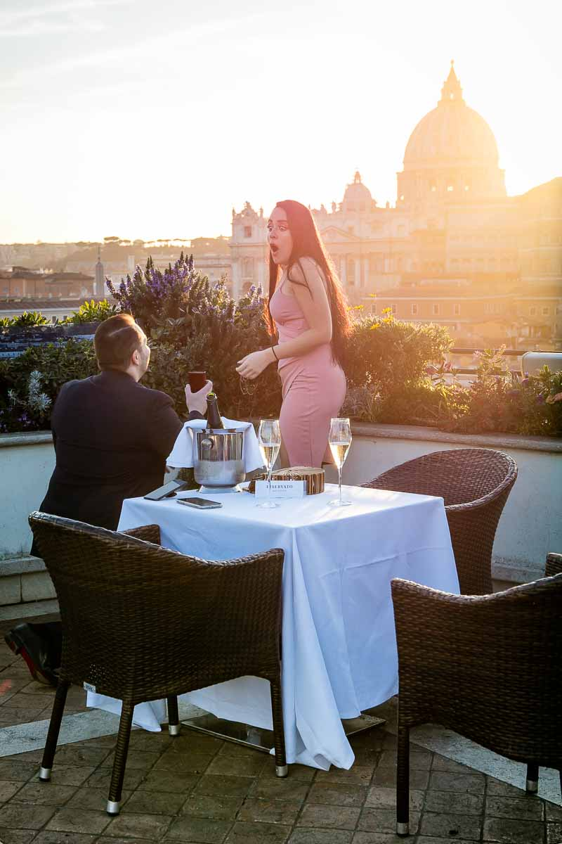 Truly surprised effect during a unique and magical proposal overlooking the city of Rome from an above terrace