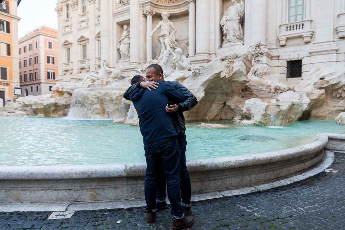 Just engaged same sex couple hugging next to the Trevi water fountain