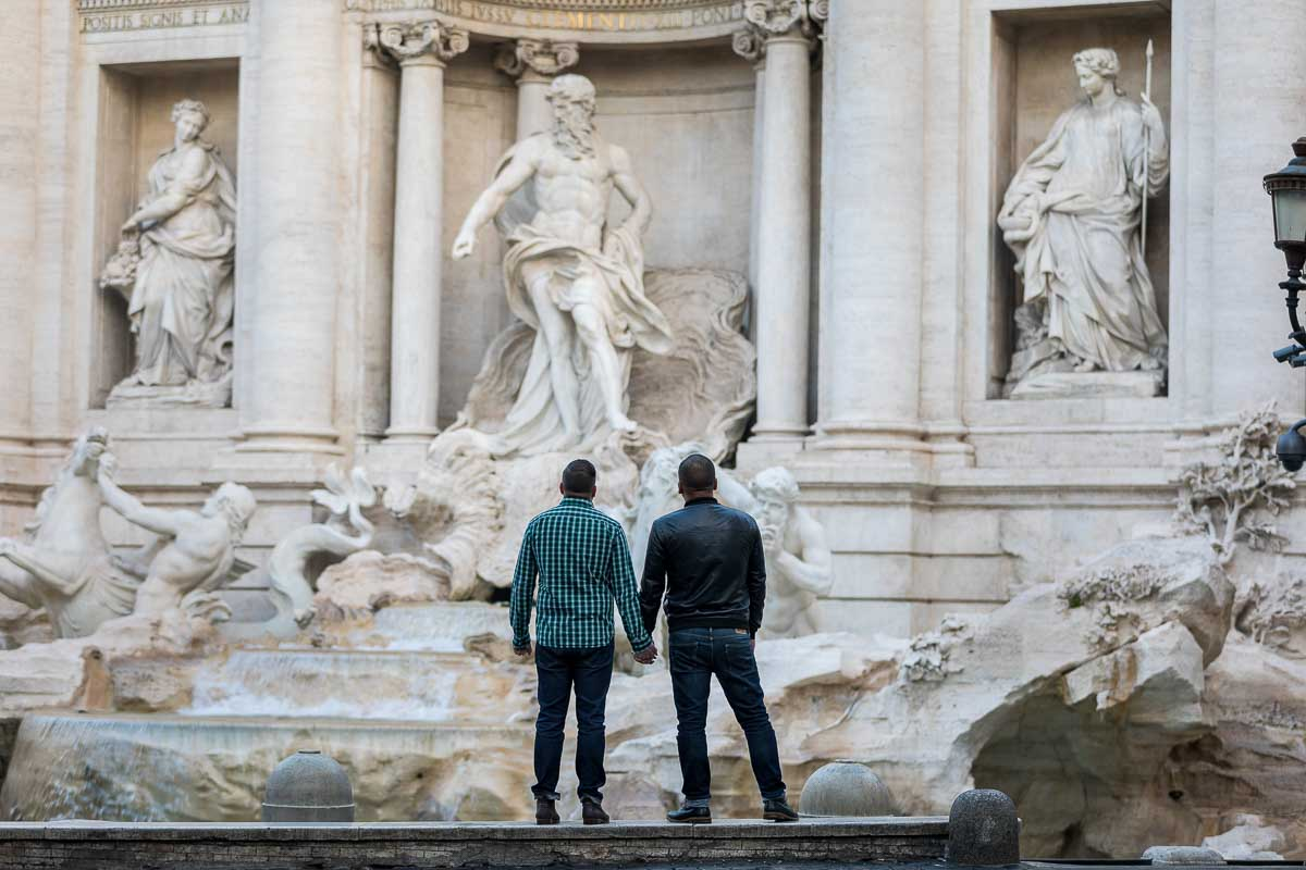 Couple holding hands and looking at the Trevi fountain marble statues from a distance