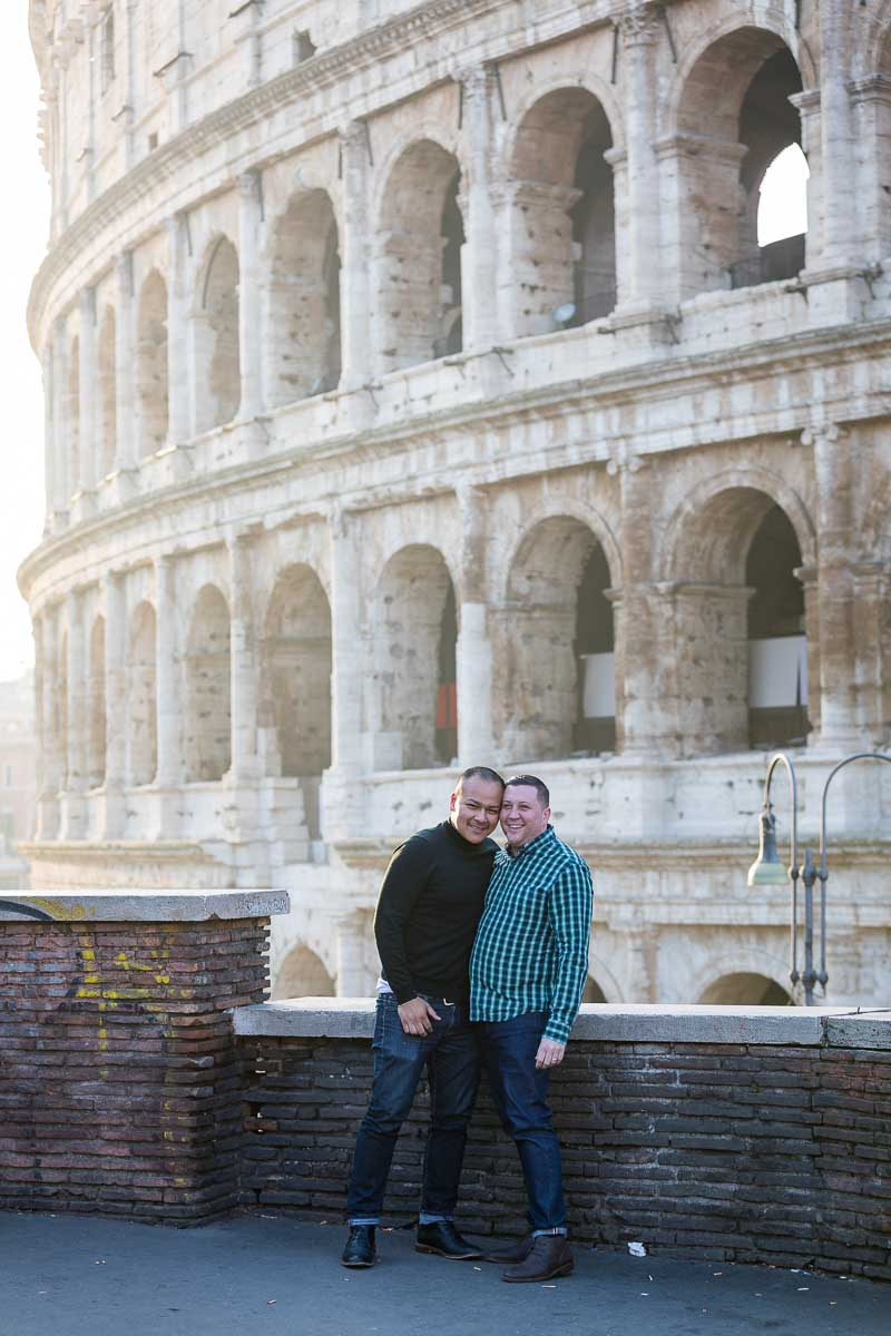 Couple close together posing in front of the Roman Colosseum