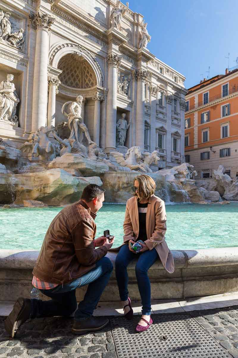 Man proposing knee down at the water edge of the Trevi fountain in the city of Rome Surprise Wedding Proposal