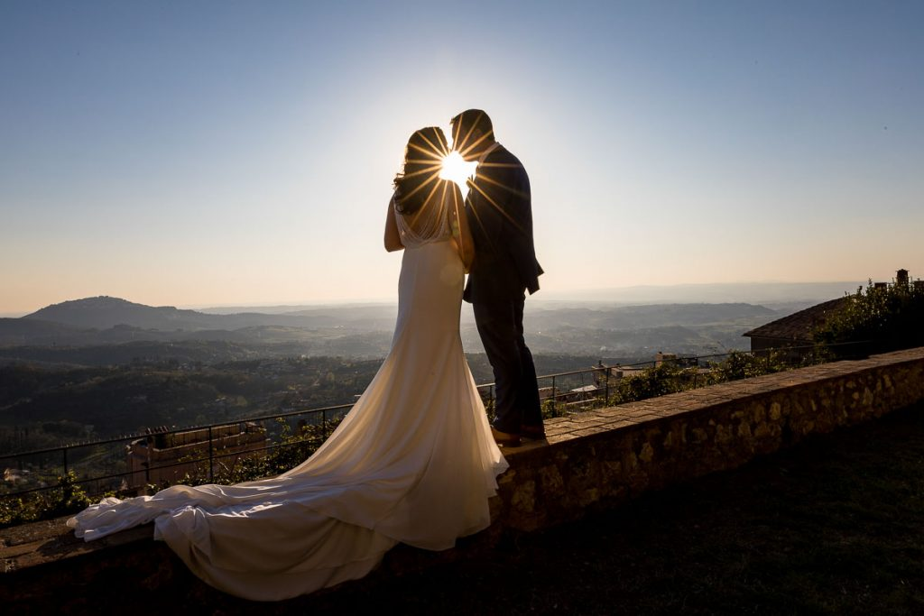 A wedding star in between the newlywed couple overlooking the Italian countryside of Palombara Sabina from Castello Savelli