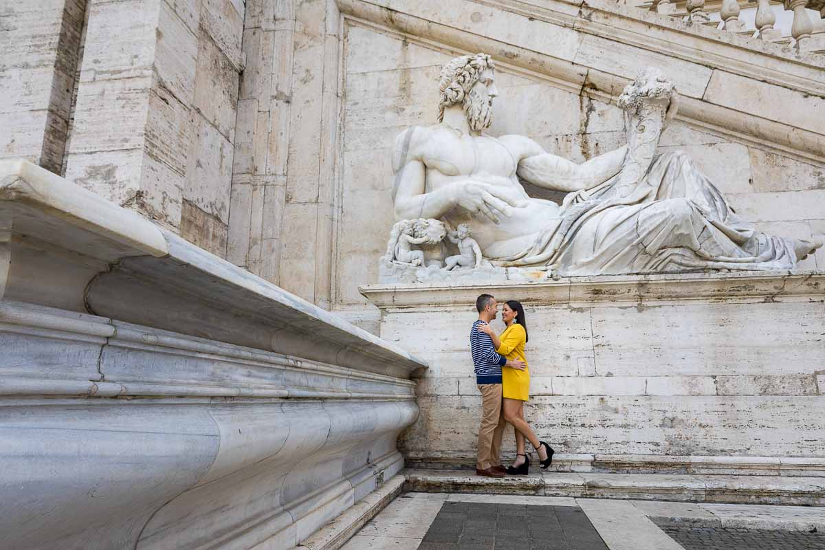 Posed photo of a couple underneath an ancient roman marble statue found in Piazza del Campidoglio