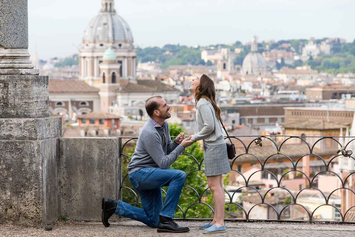 Man kneeling down during a surprise wedding proposal taking place at the scenic parco del pincio terrace in Rome Italy