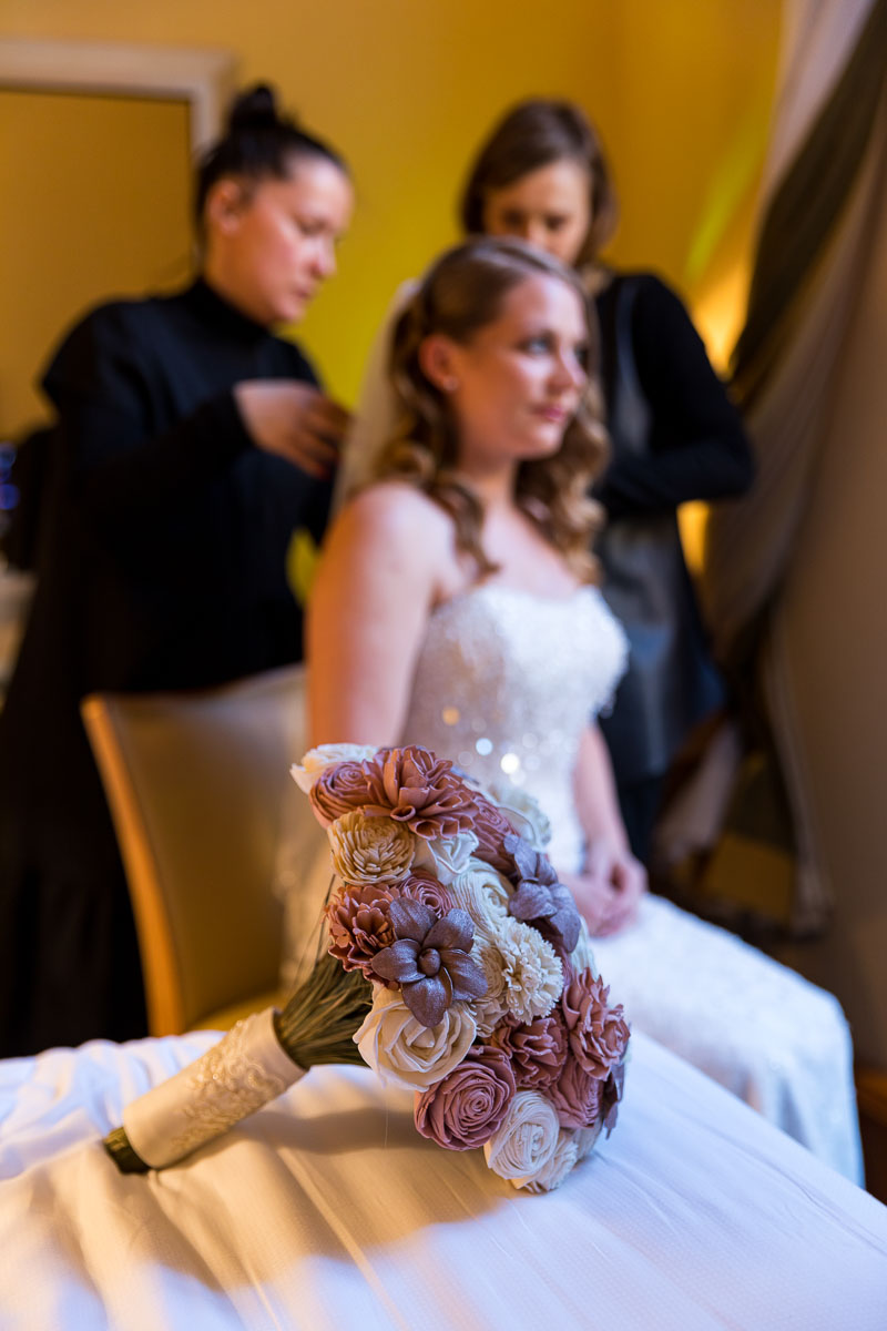 Bridal bouquet in the forefront in focus with the bride and the makeup team in the background out of focus