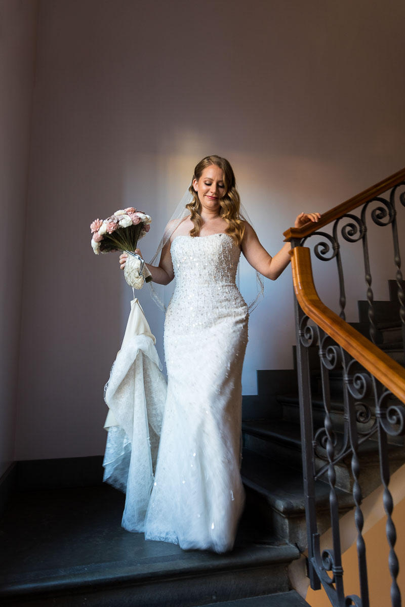 Bride descending stairs next to natural daytime light shining through the window