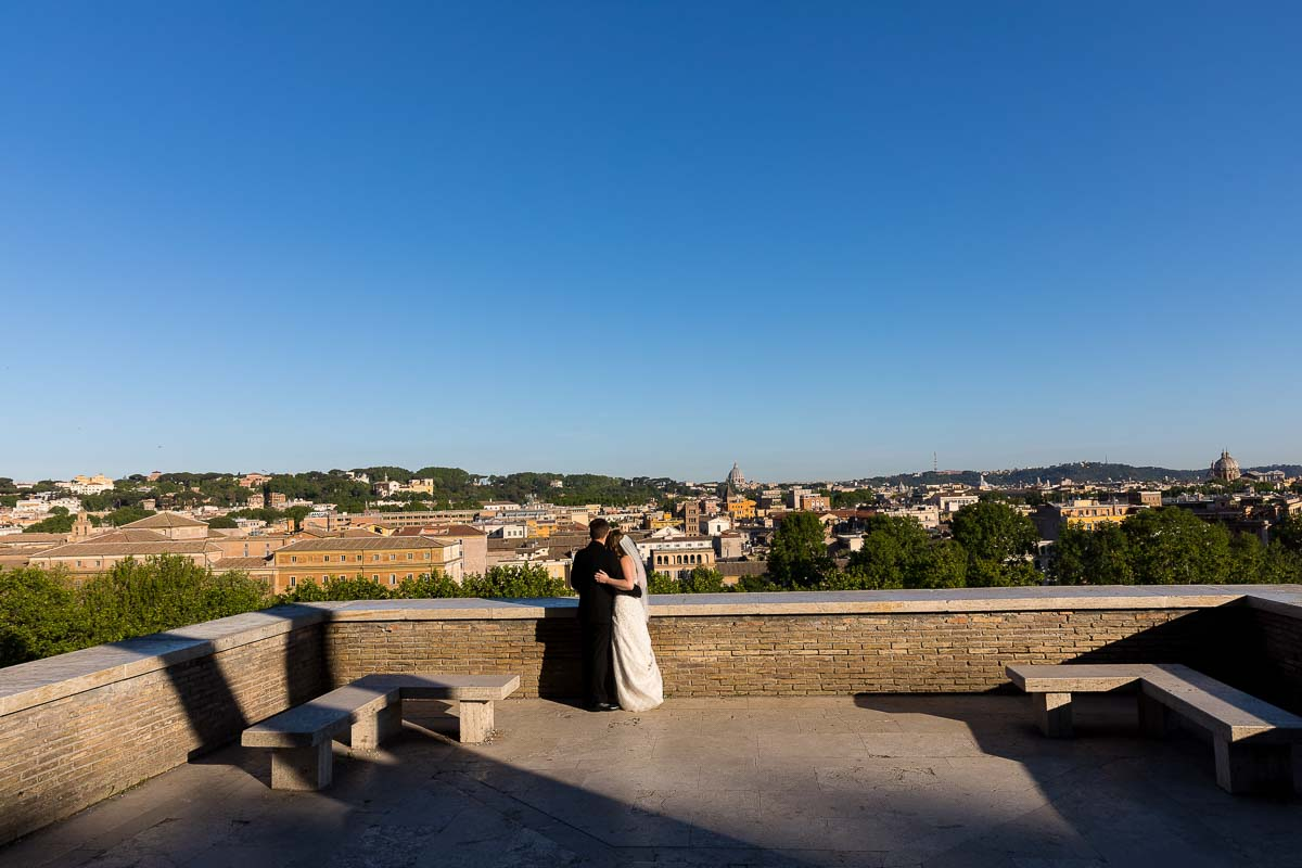 Bride and groom standing on the terrace view of Giardino degli Aranci in Rome Italy observing the panoramic view