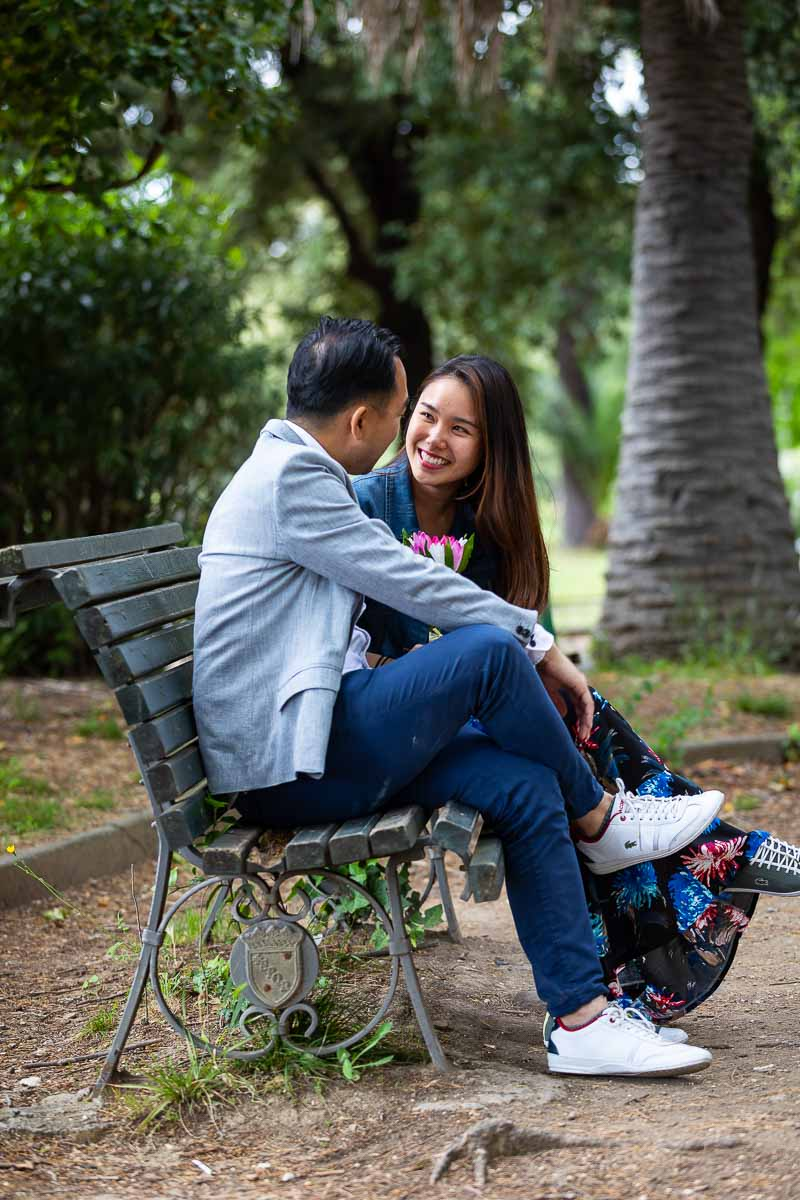 Couple sitting down on a park bench in a park like setting during a session with professional photographers