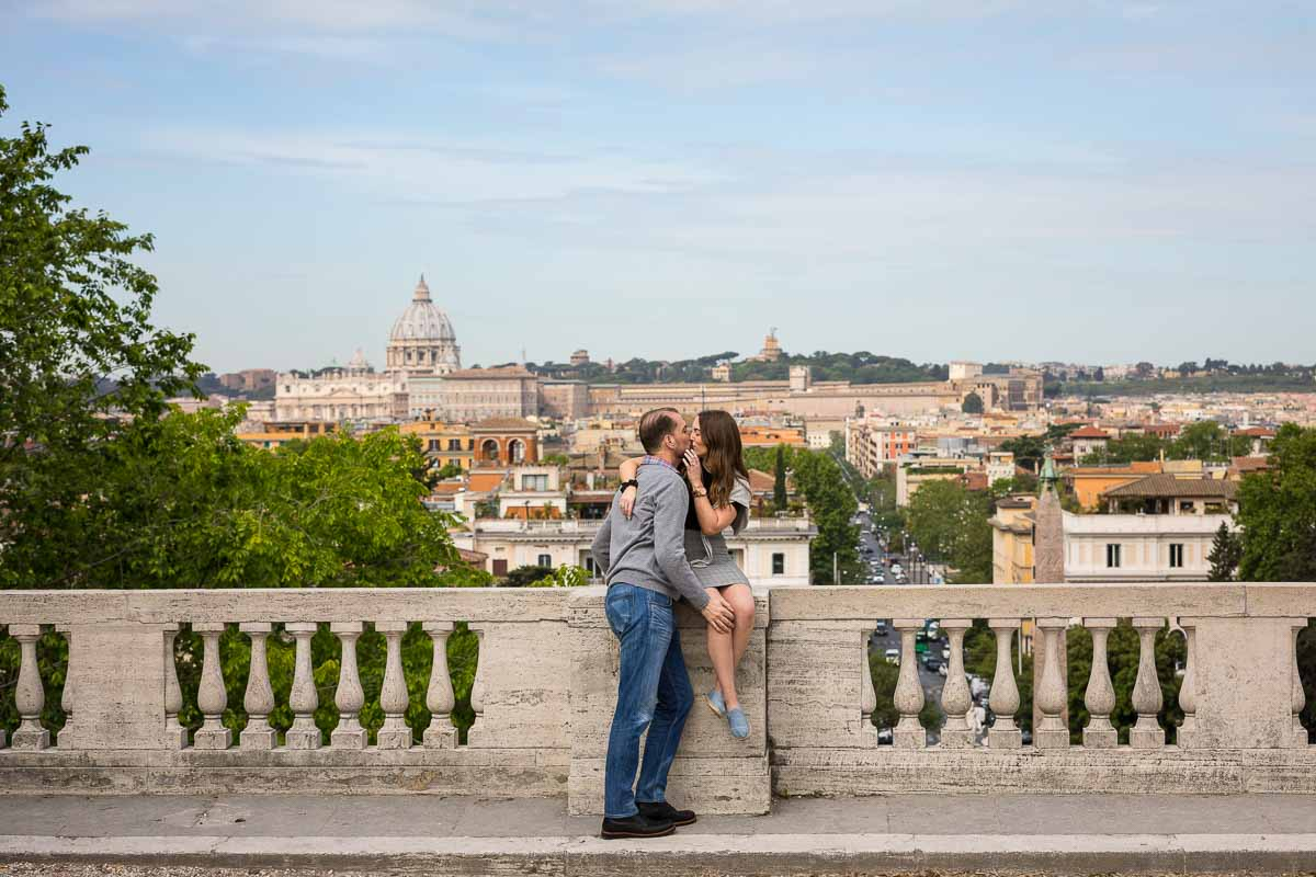 Kissing before the panoramic view of the city of Rome Italy in the background
