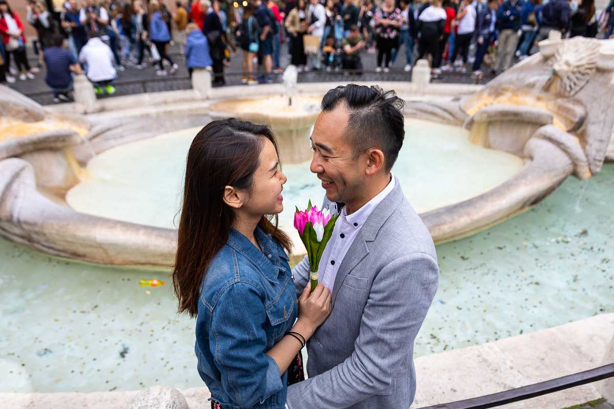 Engagement picture of a coupe close to one another before the Barcaccia water fountain found at the bottom of the Spanish steps