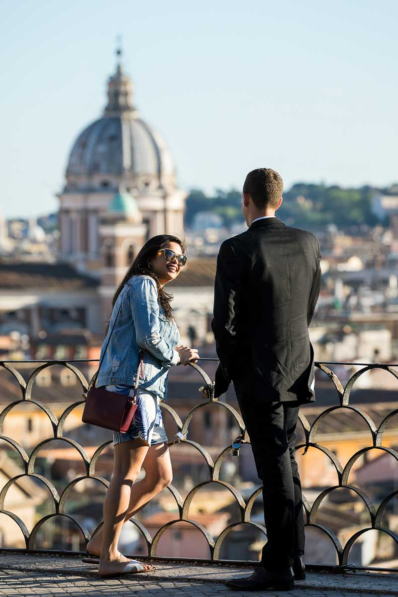 Couple talking on the terrace of the Villa Borghese park overlooking the city from a distance