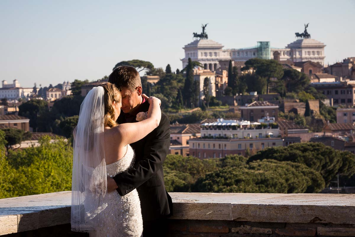 Couple posing wedding attire with the city of Rome in the far distance