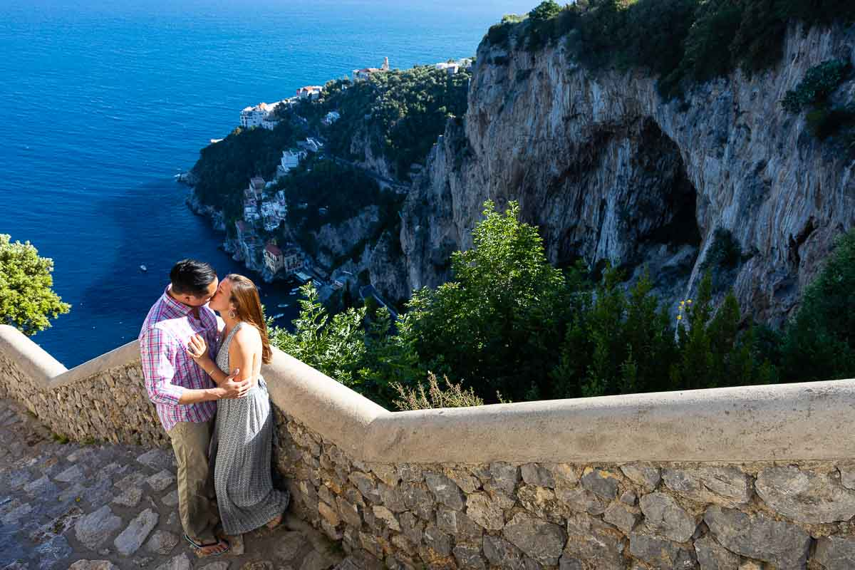 Couple kissing on a staircase before the coast view near the town of Amalfi
