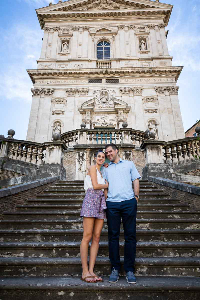Stand up portrait picture of a couple standing on the beautiful staircase leading to the church facade