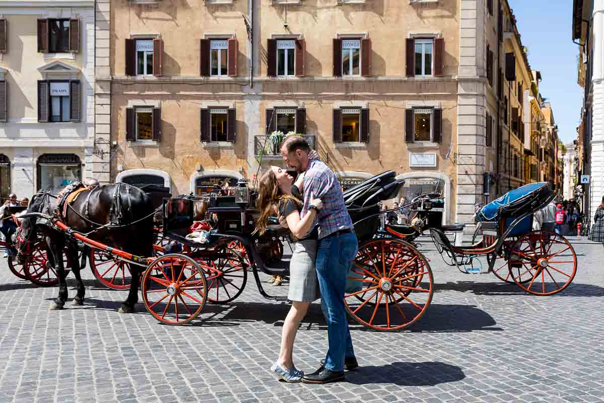 Couple in love in Piazza di Spagna with horse carriages