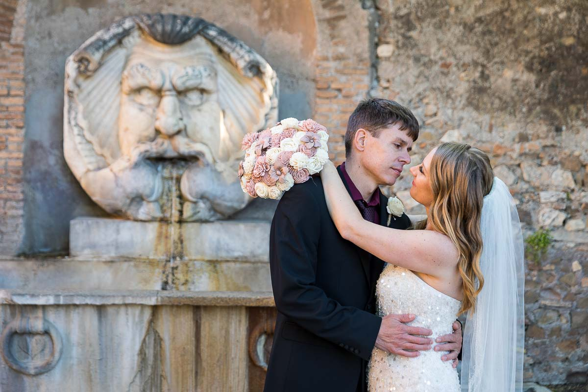 Wedding portrait before the marble statue found at the entrance of the orange garden in Rome