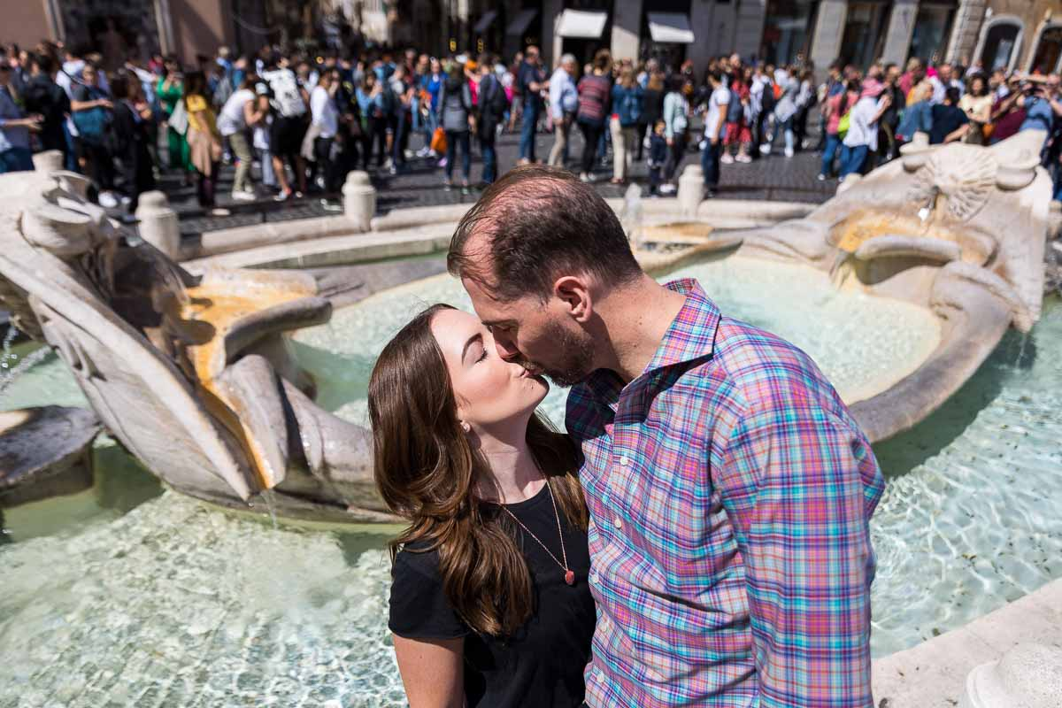 Romantic kiss by the Barcaccia water fountain found in Piazza di Spagna Rome Italy