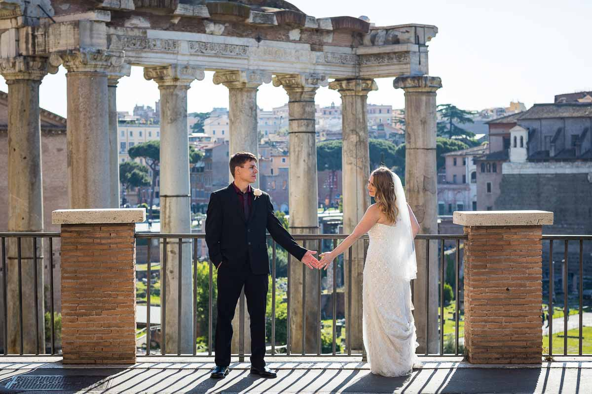 Wedding couple holding hands before the ancient scenery of the roman forum