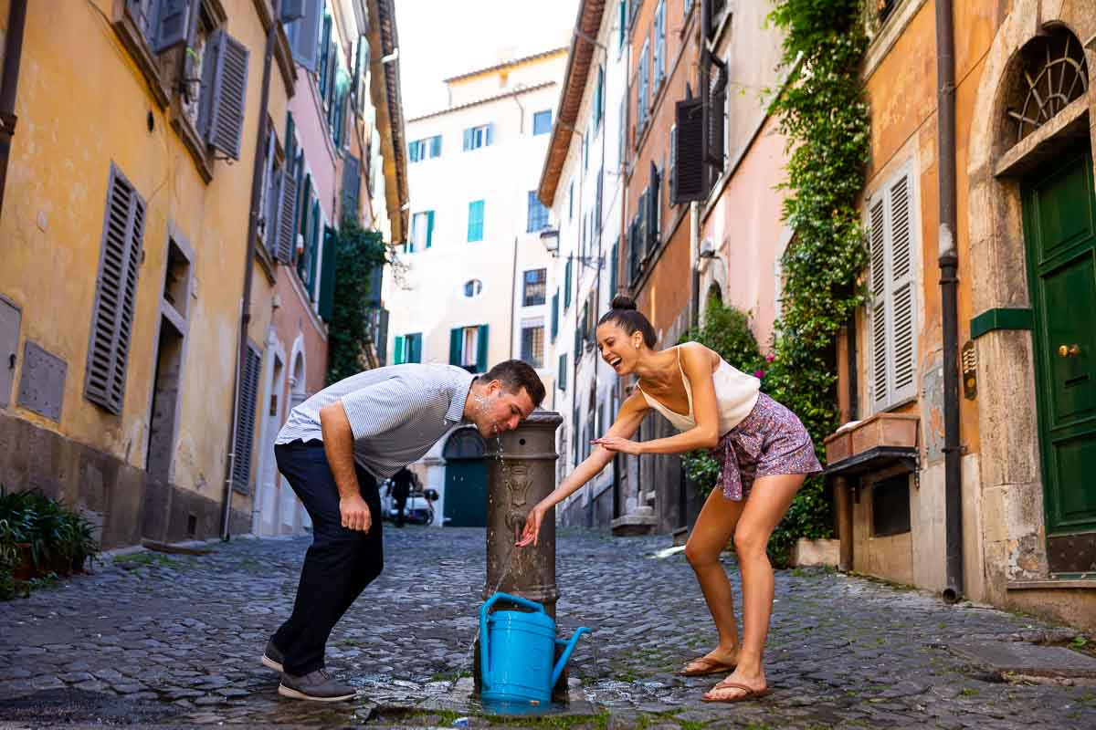 Having fun with a drinking water fountain in the roman streets