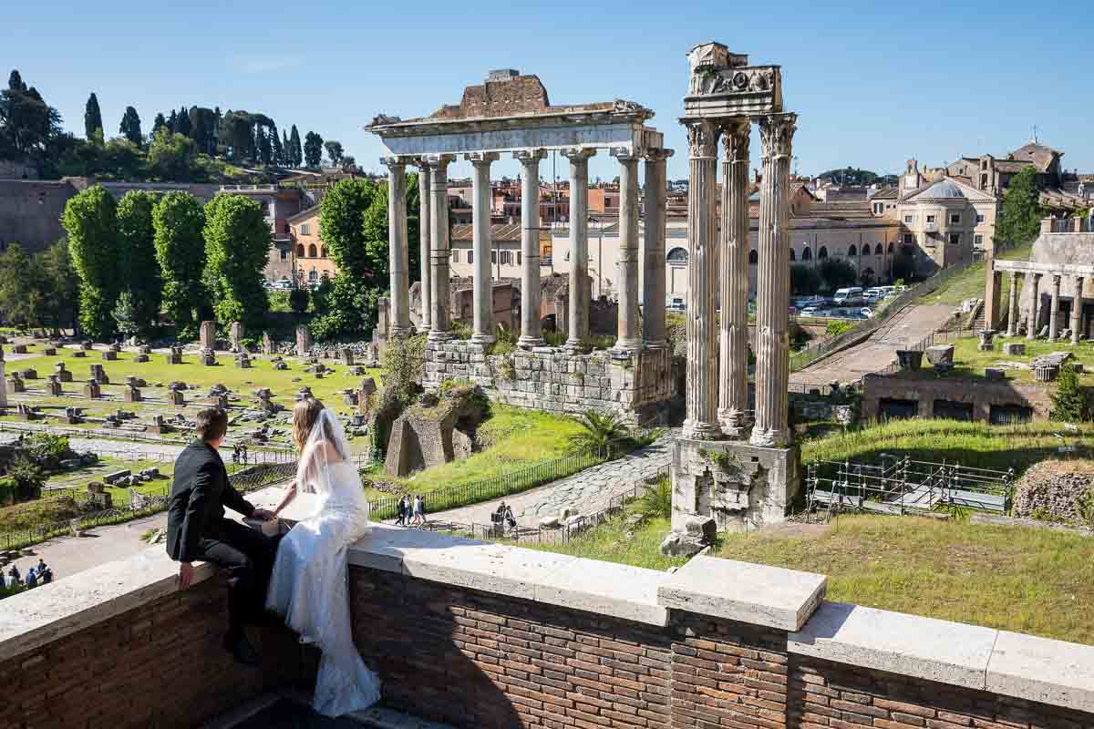 Bride and groom observing the unique and timeless view of the ancient roman ruins found at the imperial forum