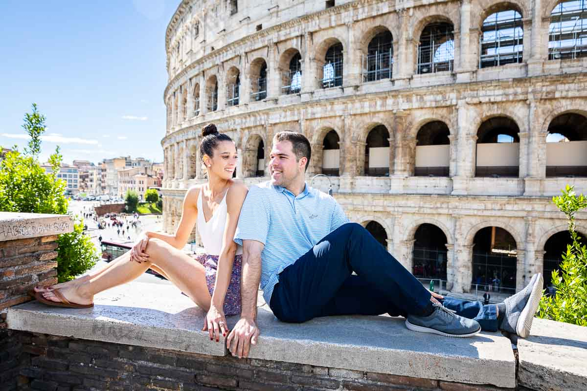 Sitting down portrait of a couple looking at each other with the coliseum in the background