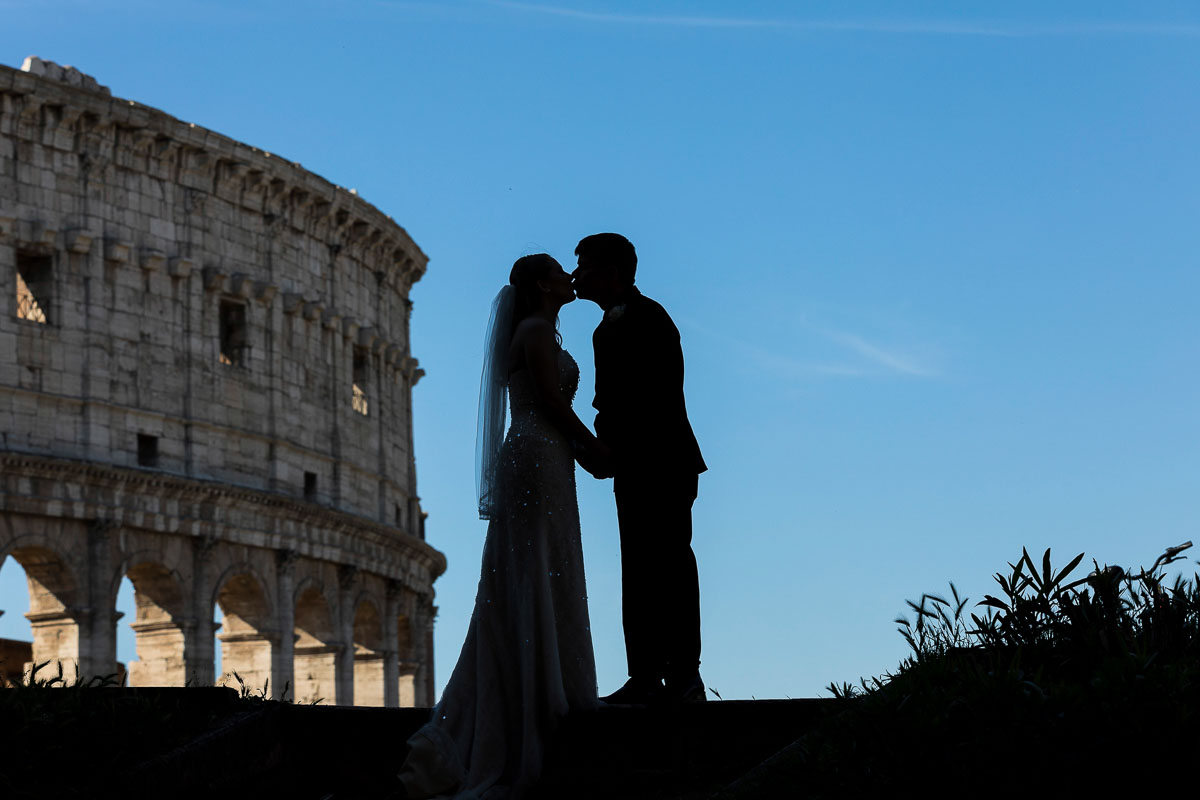 Silhouette image taken with the Roman Colosseum in the background with bright blue sky