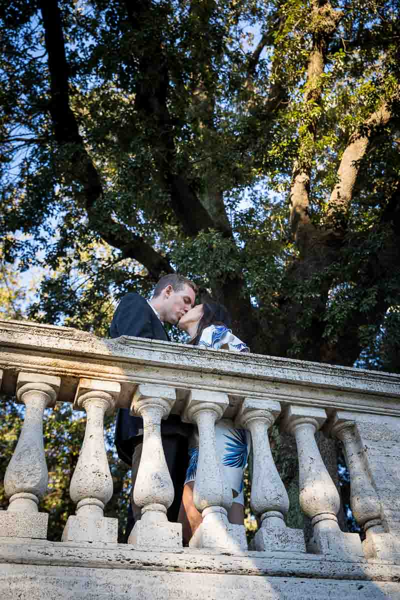 Kissing underneath a tree in the Villa Borghese park