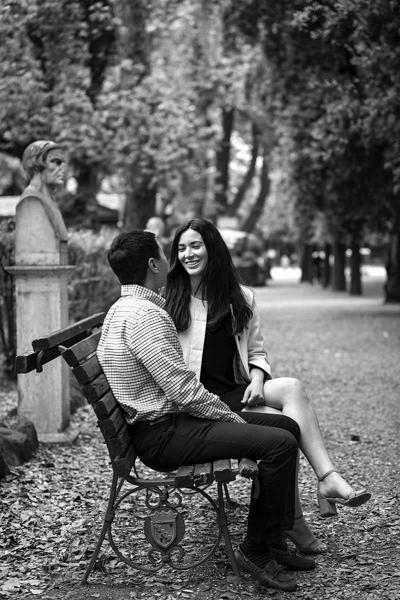 Couple sitting down on a bench during an engagement photo shoot in Villa Borghese park in Rome Italy