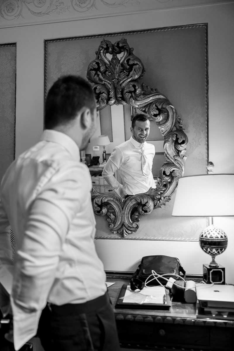 Groom getting ready for marriage in front of the mirror. Image in black and white