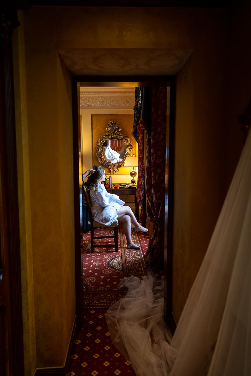 Bridal preparation image. Bride sitting down on a chair by the window. Photography taken from the hall