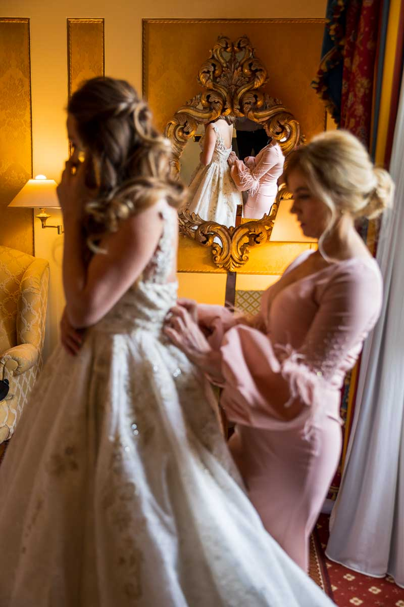 Bridesmaids helping closing the bride's wedding dress