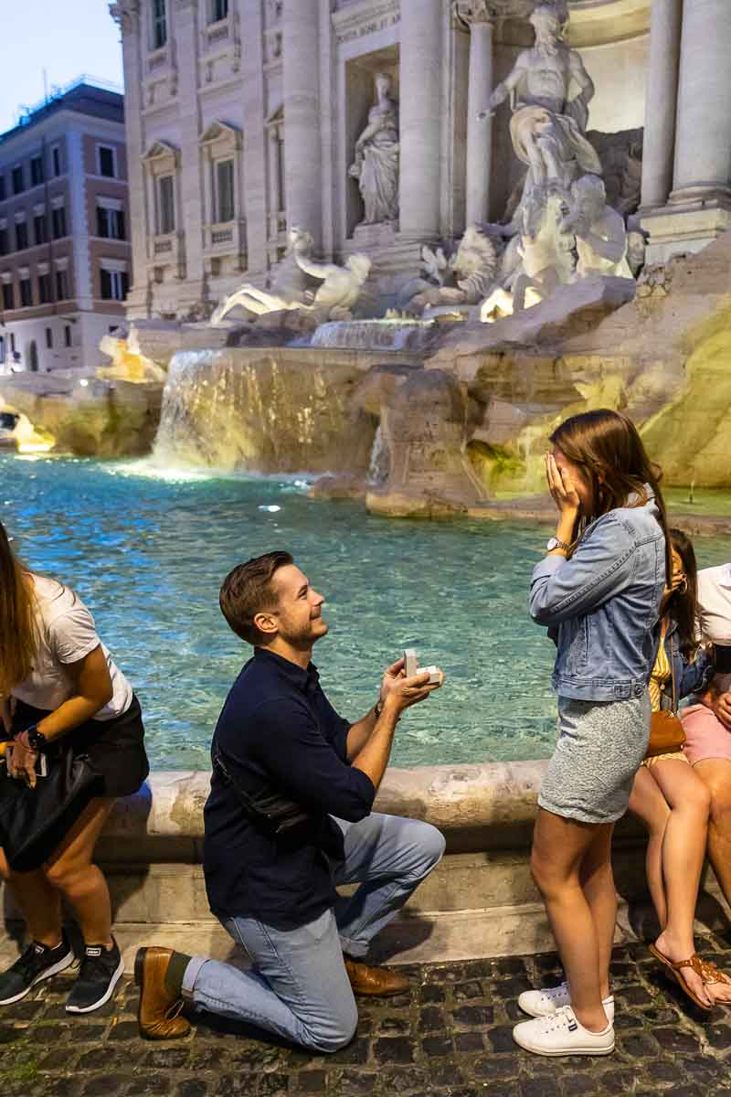 Man knee down nighttime surprise wedding proposal at the Trevi fountain. Rome night time proposal
