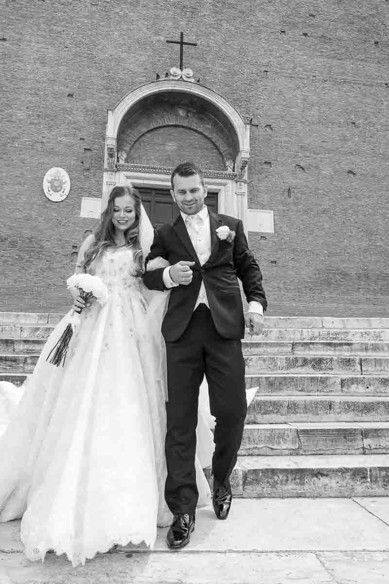 Newlyweds walking together out of the church and descending the steps of church Santa Maria in Aracoeli in black and white