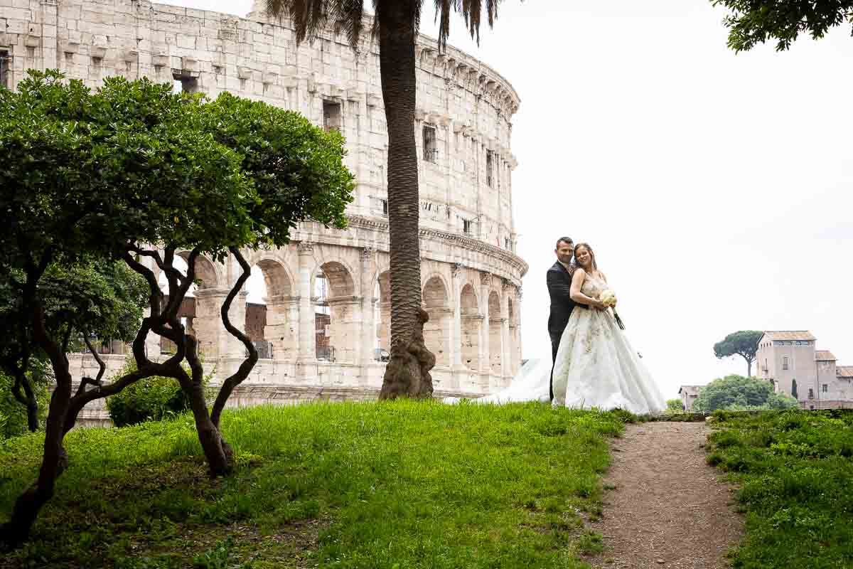 Standing in the far distance in front of the Colosseum Rome Destination Wedding