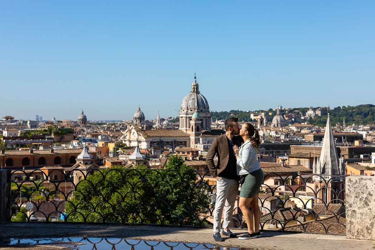 Couple kissing before the roman skyline