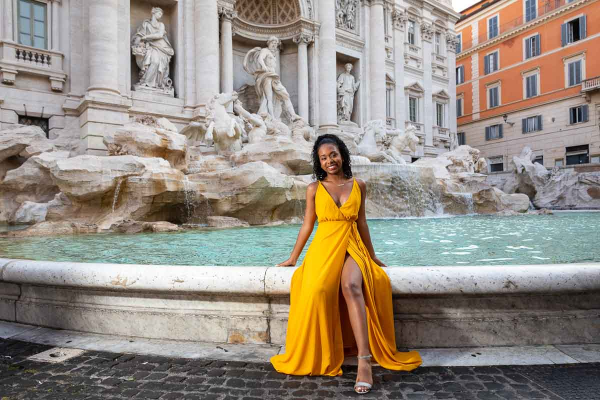 Yellow dress girl posed while sitting on the fountain edge