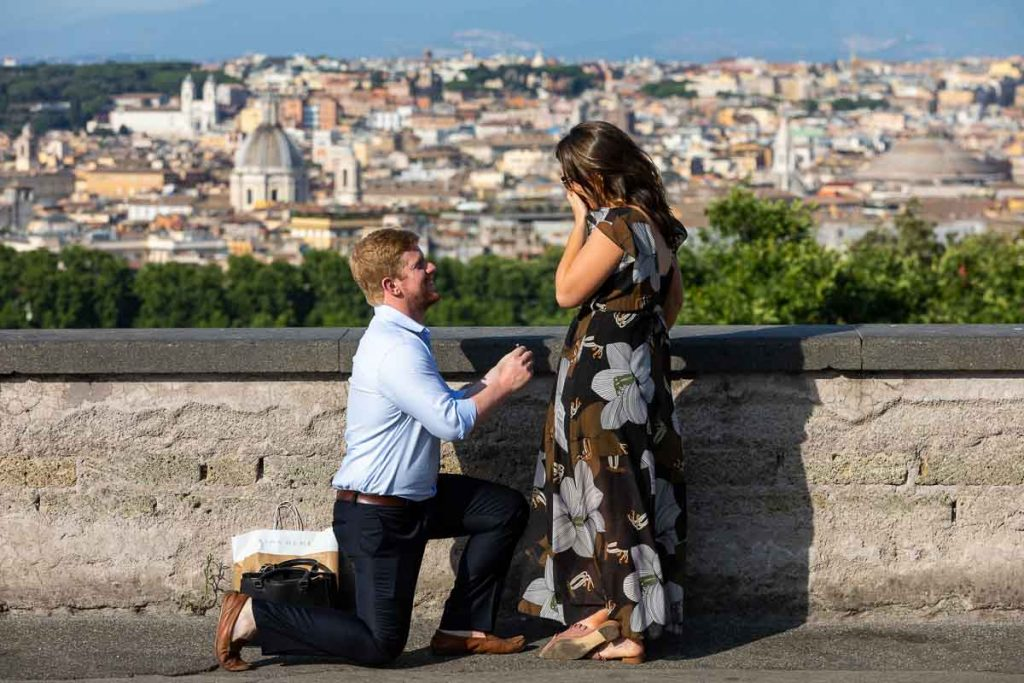 Man kneeling down proposing wedding overlooking the scenic view of the Rome panorama in the background.