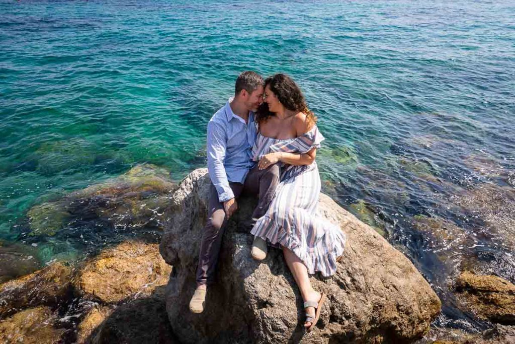 Capri engagement photo session. Couple sitting down on the rocks surrounded by crystalline emerald green blue water all around