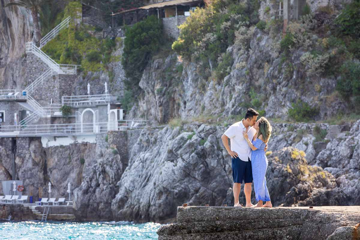 Distance image of a couple kissing while standing on the beach marina of Amalfi