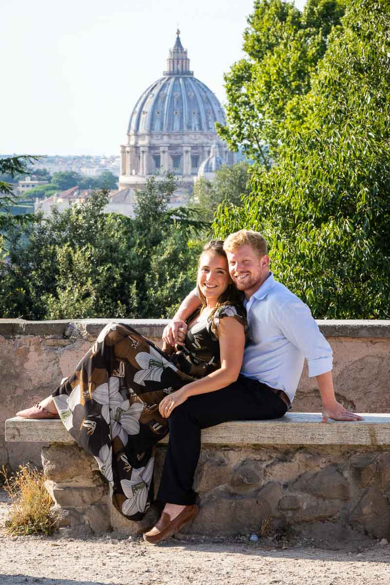 Couple portrait sitting down on a marble bench with St. Peter's Cathedral dome in the background