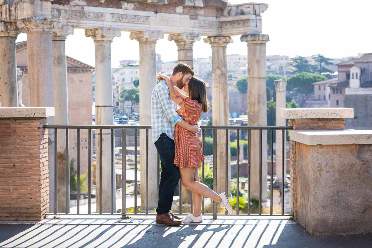 Kissing in ancient Rome. Photo shoot taking place in Piazza del Campidoglio with a unique view over the ancient temple columns