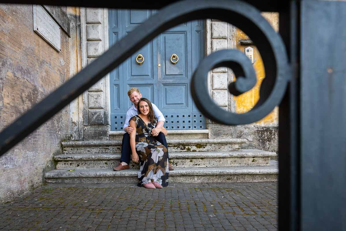 Creative portrait photography couple sitting down before a nice door in Rome