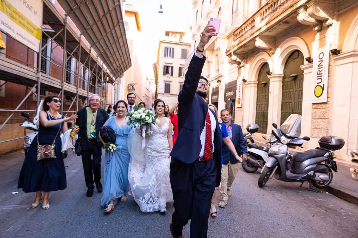 Wedding party walking together towards the Trevi fountain together