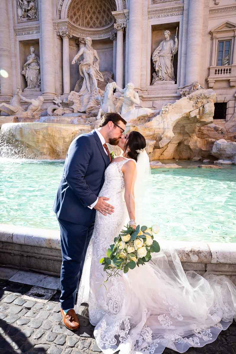 Trevi fountain groom and bride kissing in front of the water fountain