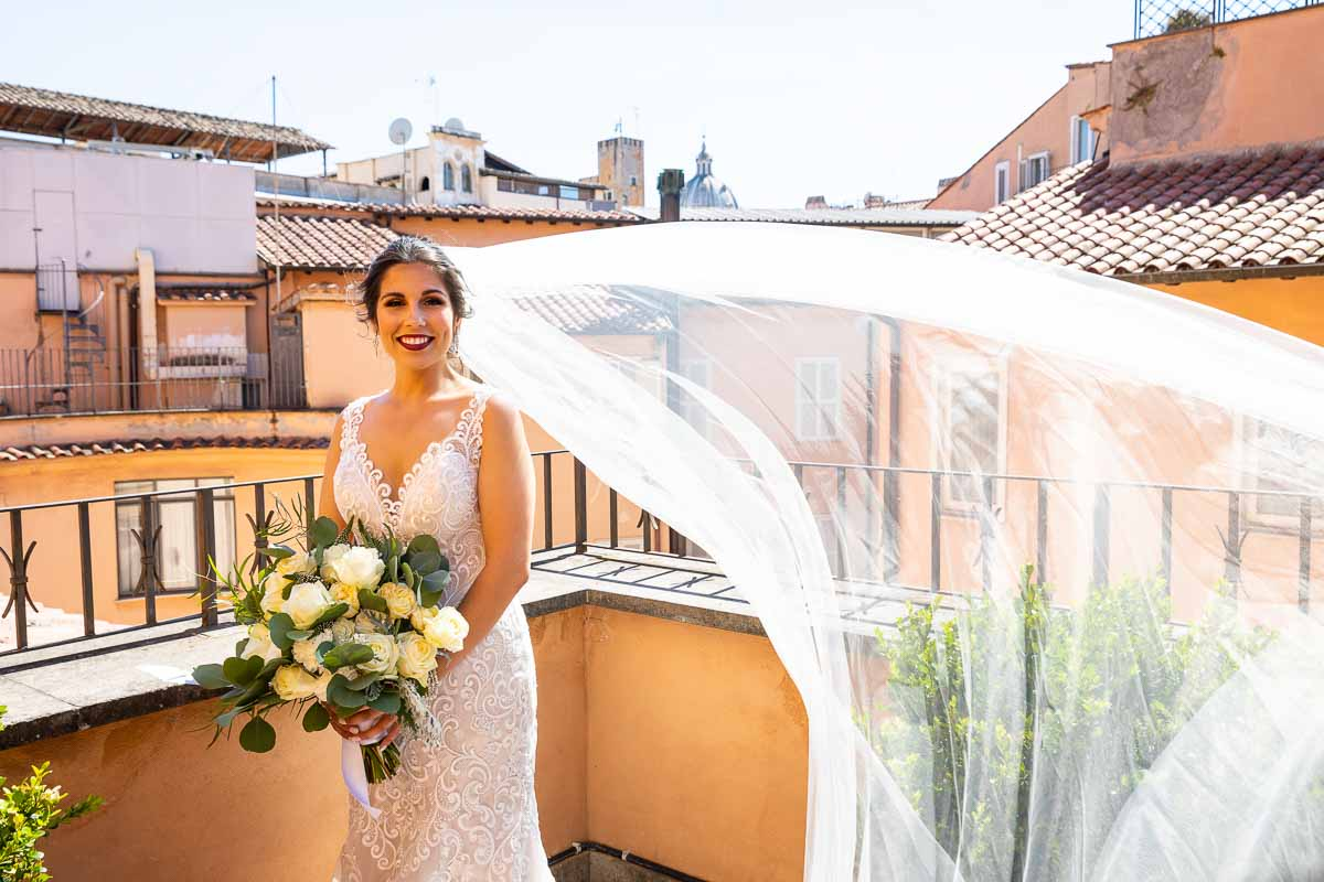 Outside balcony Bride photo with the wedding veil flying up in the air