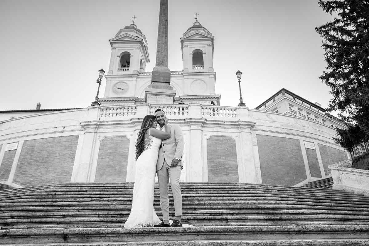 Black & White image of a couple in wedding attire posing on Rome's Spanish steps