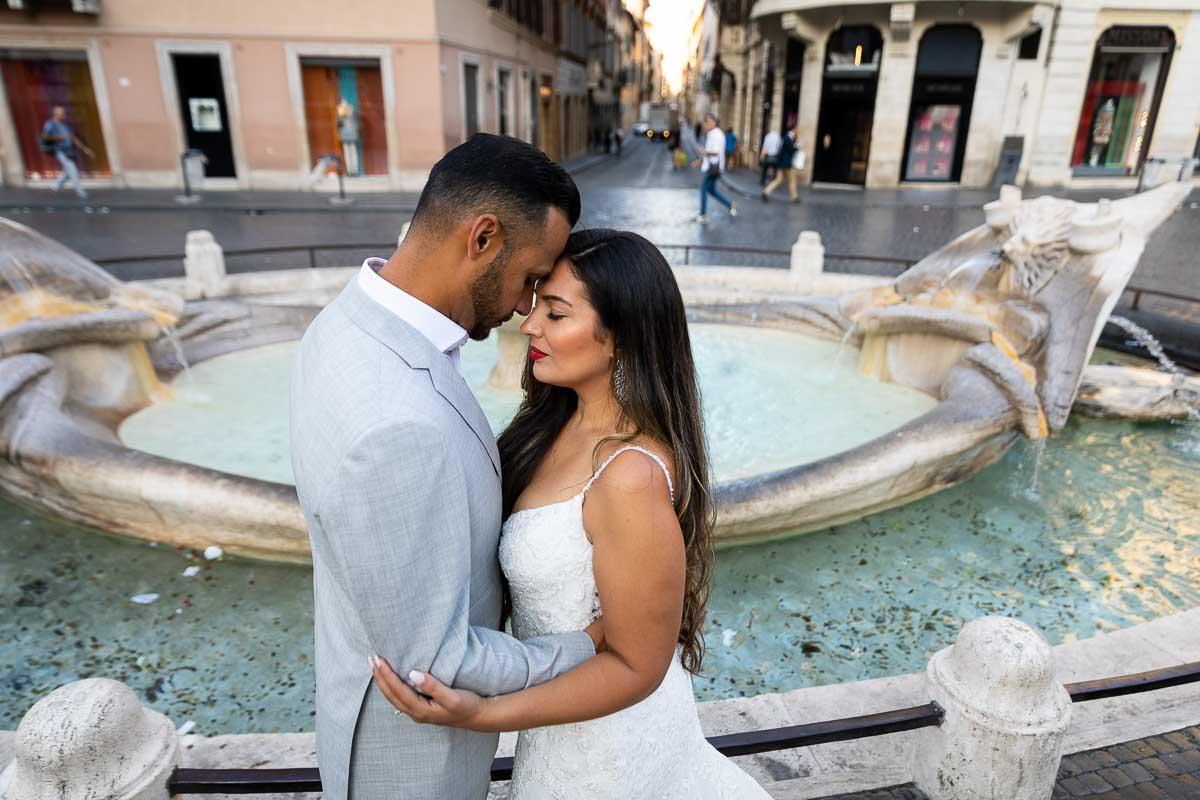 Couple image resting forehead to forehead in front of the barcaccia water fountain
