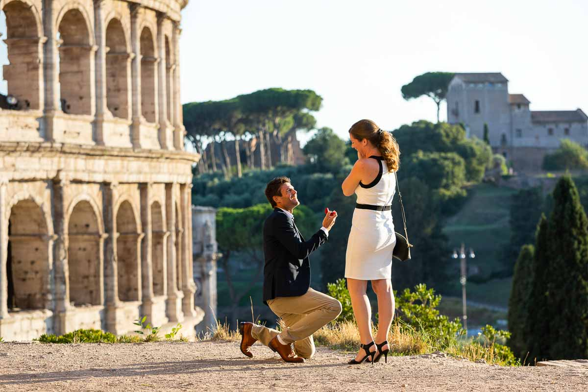 Man kneeling down for a Colosseum proposal in Rome candidly photographed at a distance by a professional photographer.
