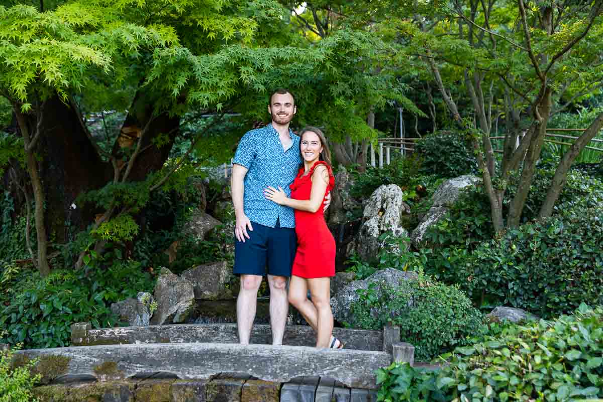 Couple portrait picture posed on the wooden bridge of the Japanese garden
