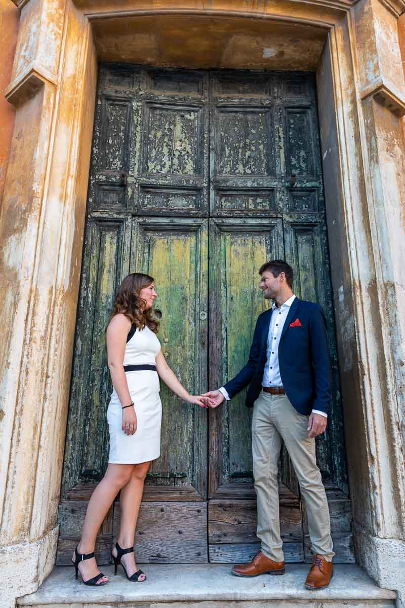 Holding hands in front of an old green church doorway